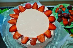 Place a ring of sliced strawberries along the outer edge of the top of the cake.